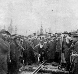 A crowd of people surround a man leaning forward.