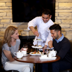 Two people having tea as a waiter serves pastries.