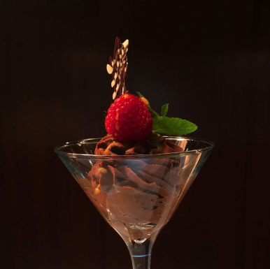 A dessert in a cocktail glass topped with a raspberry.