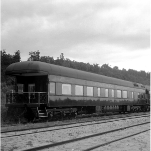 A black and white photo of the outside of a train.