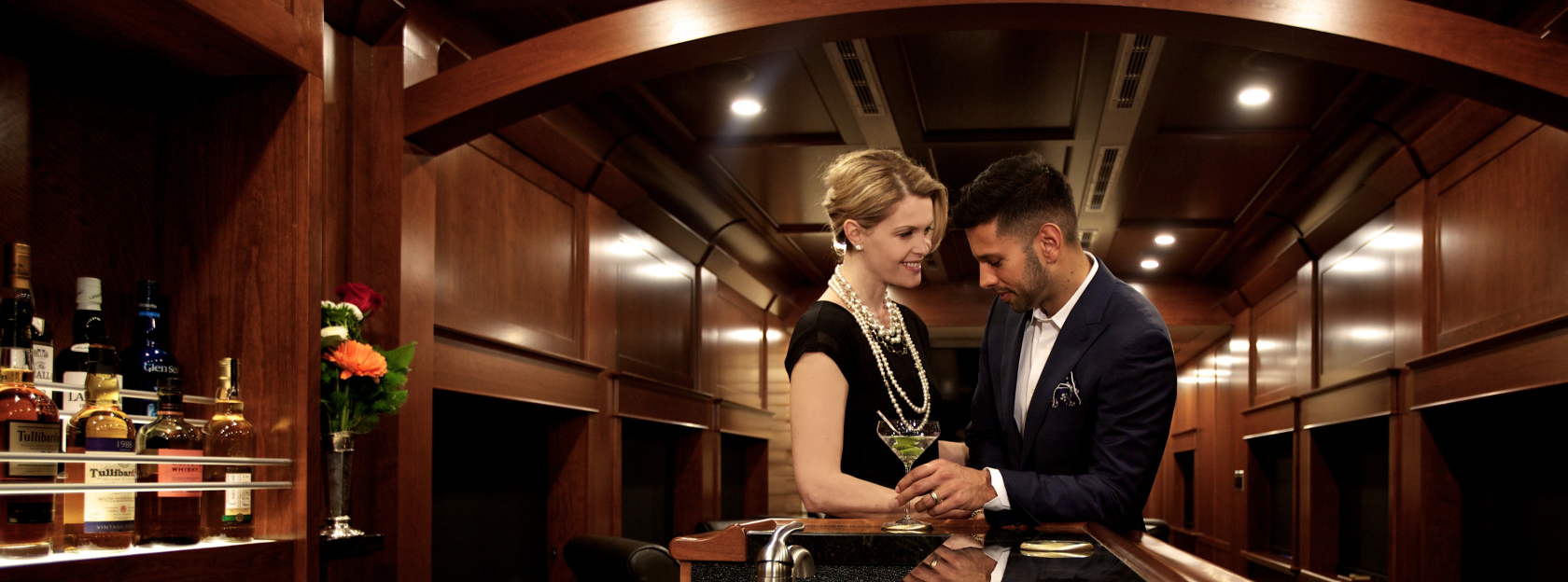 Two people dressed in formal attire at a bar inside of a rail car.