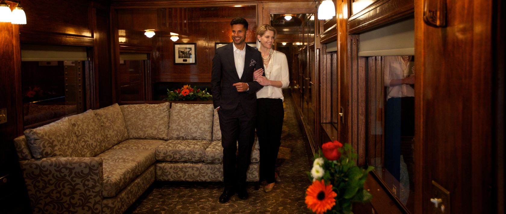 A man and a woman stand in a lounging area inside of a rail car.