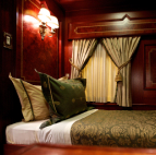 A queen bed next to a set of curtains covering a window in a train car.