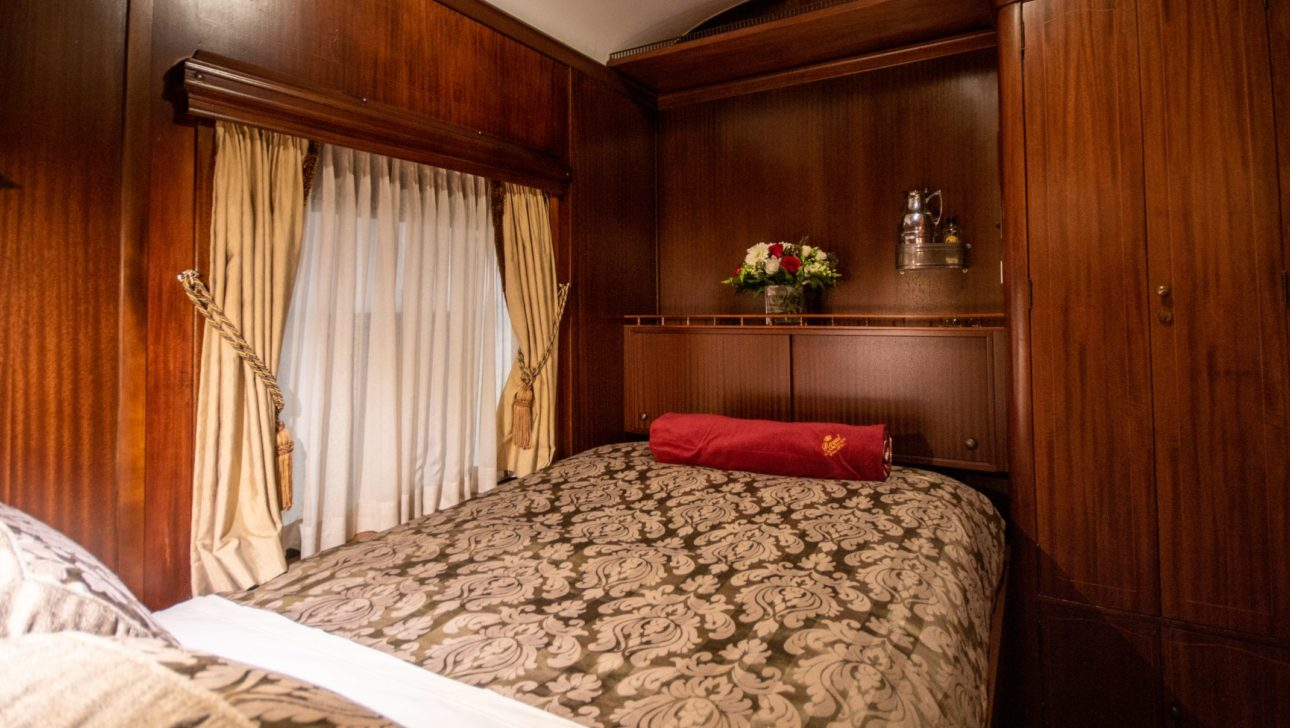 Queen sized bed in a train car.