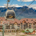 An empty gondola lift moving up, with a resort and mountains in the background.