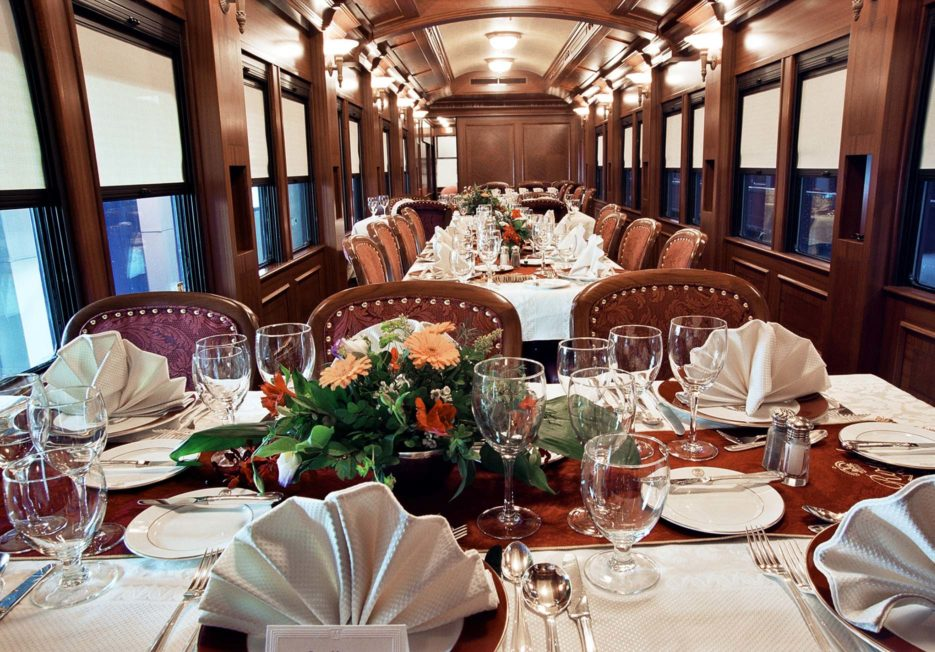 Fully set dining tables inside a railcar.