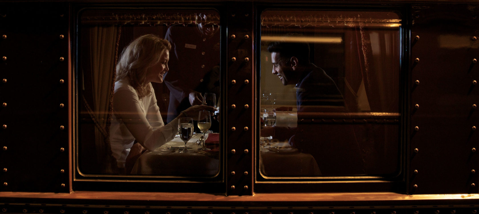 A couple smiling as they have a meal in a railcar.