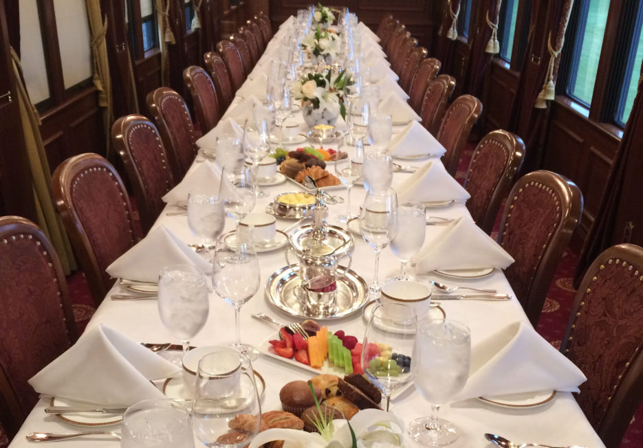 A long, set dining table inside of a railcar.