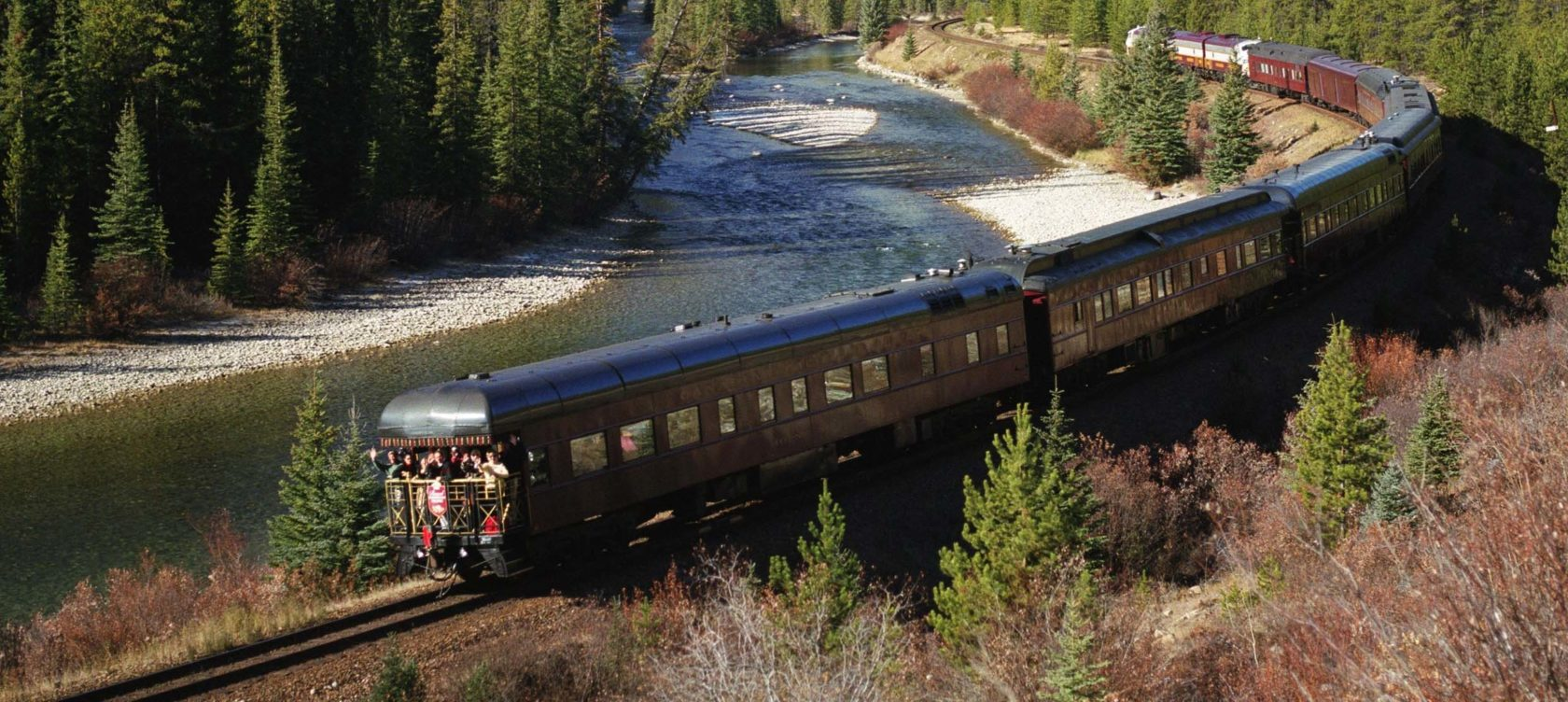 A train moving alongside a river and a forest.